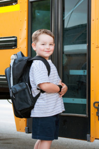 happy boy walking into school bus